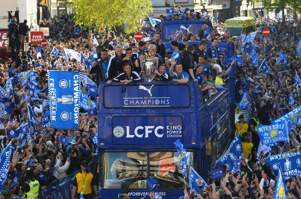 Leicester City's Italian manager Claudio Ranieri (C) stands with the Premier league trophy as the Leicester City team take part in an open-top bus parade through Leicester to celebrate winning the Premier League title on May 16, 2016. / AFP PHOTO / GLYN KIRKGLYN KIRK/AFP/Getty Images